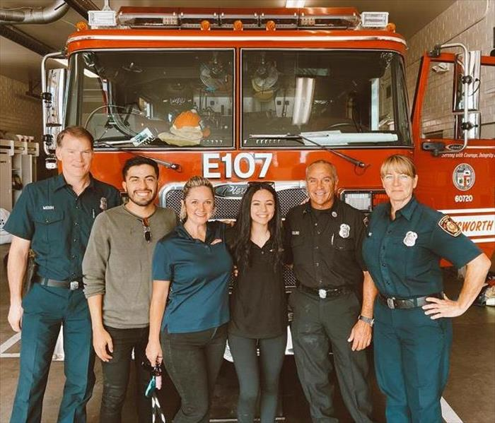 3 staff posing with some firefighters